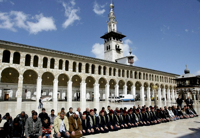 People pray in the Omayyad mosque courtyard during the funeral ceremony of Sunni Muslim cleric Mohamed Saeed al-Bouti, who died in a suicide bomb attack, on March 23, 2013 in the Syrian capital Damascus. (AFP Photo / Louai Beshara)