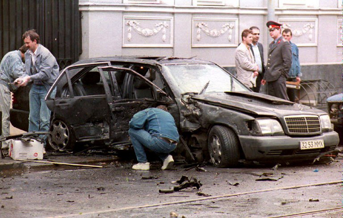 """Police experts examine the remains of the car belonging to Boris Berezovsky, chairman of the Russian auto concern, """"LOGOVAZ,"""" whose driver was killed when the tycoon's Mercedes was blown up in Moscow 07 June 1994. (AFP Photo / Alexey Iliyn)"""