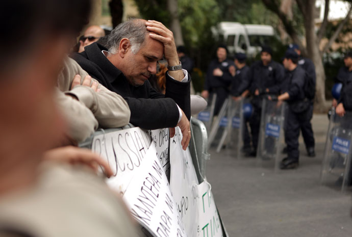 An employee of Cyprus Laiki (Popular) Bank reacts as he takes part in a protest outside the parliament in Nicosia.(AFP Photo / Patrick Baz)