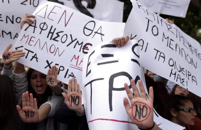 "Cypriot college students shout slogans while showing their palms reading ""No"" during a protest in Nicosia against a bailout for the financially crippled island on March 26, 2013. (AFP Photo / Patrick Baz)"