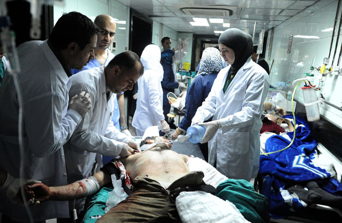 A handout picture released by the Syrian Arab News Agency (SANA) shows an injured people being treated in the emergency room of a hospital following an alleged mortar attack that hit the Baramkeh district of Damascus on March 26, 2013.(AFP Photo / SANA)