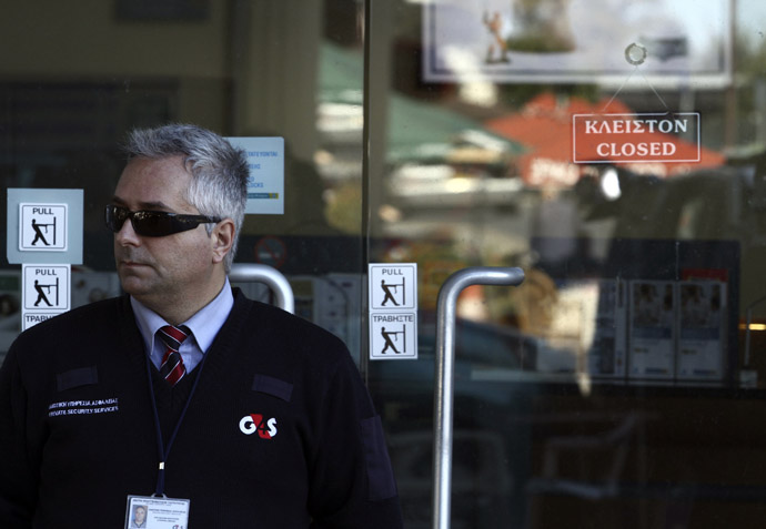A security man stands outside a closed Laiki bank branch in the Cypriot capital, Nicosia, on March 28, 2013, ahead of their reopening after an unprecedented 12-day lockdown. (AFP Photo)