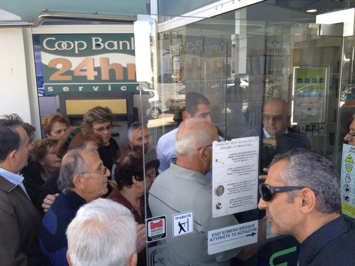 Banks in Cyprus open at 12:00 GST. People crowd the doors to access their savings for the first time in twelve days (Image from Twitter/@willgoodbody)
