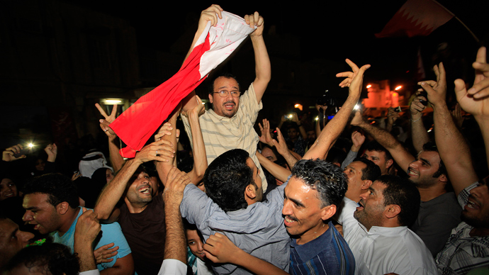 Bahraini doctor Ali al-Akri holds up a Bahrain flag as he is embraced by anti-government protesters upon arriving home in Manama, September 7, 2011 (Reuters / Hamad I Mohammed)