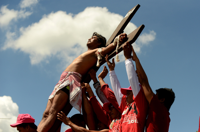 A penintent is nailed to the cross during the reenactment of crucifixion on Good Friday in the village of San Juan, San Fernando City, north of Manila on March 29, 2013 (AFP Photo / Noel Celis)