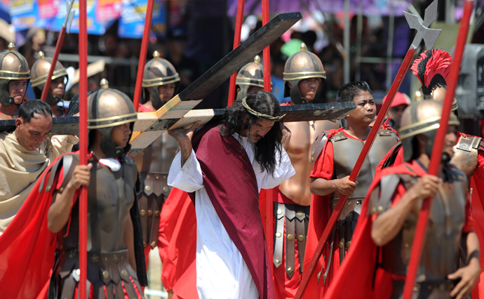 Philippine Christian devotee Ruben Enaje (C), carries a wooden cross during a re-enactment of the crucifixion of Jesus Christ on Good Friday in San Fernando City, Pampanga province, north of Manila on March 29, 2013 (AFP Photo / Noel Celis)