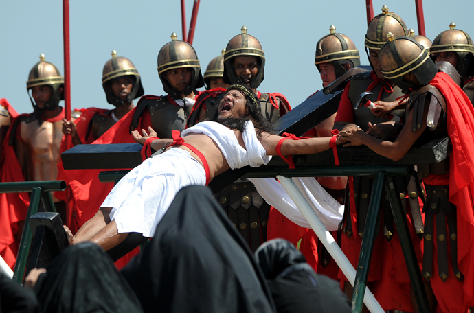 Philippine Christian devotee Ruben Enaje (C), grimaces in pain as he is nailed to the Cross by men dressed as Roman soldiers during a re-enactment of the crucifixion of Jesus Christ on Good Friday in San Fernando City, Pampanga province, north of Manila on March 29, 2013 (AFP Photo / Noel Celis)