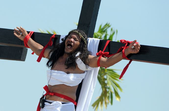 Philippine Christian devotee Ruben Enaje grimaces in pain after being nailed to the Cross by men dressed as Roman soldiers during a re-enactment of the crucifixion of Jesus Christ on Good Friday in San Fernando City, Pampanga province, north of Manila on March 29, 2013 (AFP Photo / Noel Celis)