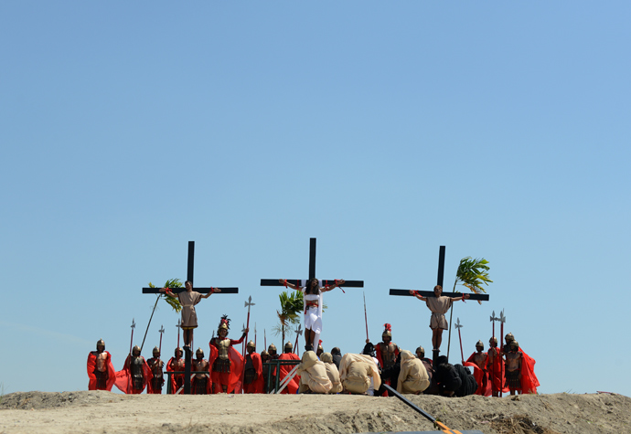 Philippine Christian devotee Ruben Enaje (C), is nailed to a cross during a re-enactment of the crucifixion of Jesus Christ on Good Friday in San Fernando City, Pampanga province, north of Manila on March 29, 2013 (AFP Photo / Noel Celis)