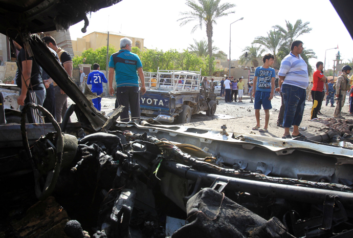 A picture taken from the inside of a damaged car shows Iraqis gathering at the site of car bomb explosion near a Shiite islamic center in the Baghdad neighbourhoods of Qahira on March 29, 2013 (AFP Photo / Ali Al-Saadi)