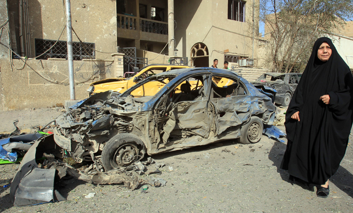 An Iraqi woman walks past a damaged car after a car bomb explosion near a Shiite islamic center in the Baghdad neighbourhoods of Qahira on March 29, 2013 (AFP Photo / Ali Al-Saadi)