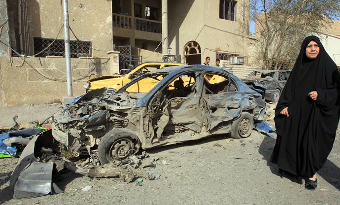 An Iraqi woman walks past a damaged car after a car bomb explosion near a Shiite islamic center in the Baghdad neighbourhoods of Qahira on March 29, 2013 (AFP Photo / Ali Al-Saadi)