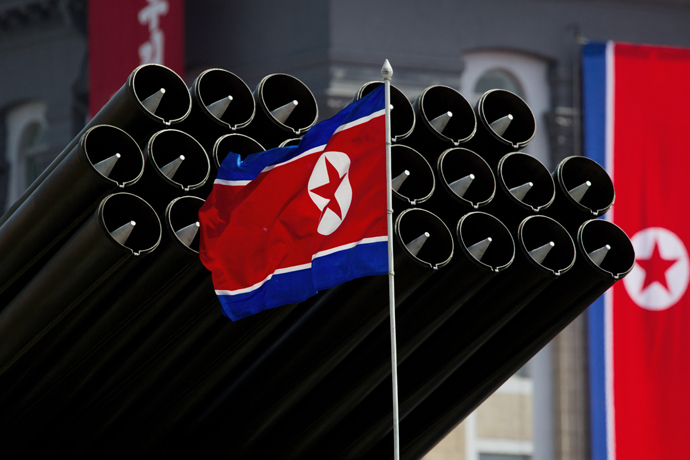 A North Korean flag flies before missiles displayed (AFP Photo / Ed Jones)