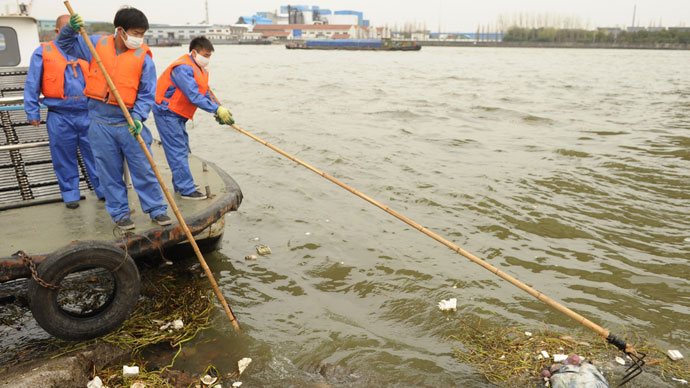 Sanitation workers (L) collect a dead pig from Shanghai's main waterway.(AFP Photo / Peter Parks)