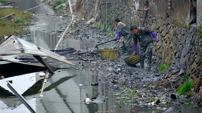 Workers clear away rubbish along a river in Rui'an, Zhejiang province.(Reuters / China Daily)