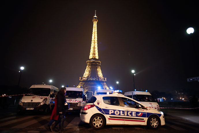 People walk past police cars blocking the way to the Eiffel Tower in Paris on March 30, 2013. (AFP Photo / Thomas Coex)