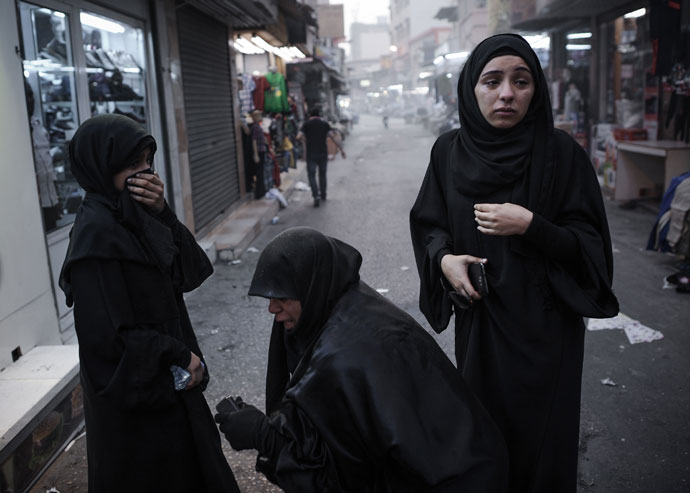 Bahraini women react after inhaling tear gas fired by riot police during an anti-regime rally in solidarity with jailed human rights activist Nabeel Rajab and against the upcoming Bahrain Formula One Grand Prix in Manama on March 29, 2013.(AFP Photo / Mohammed AL-Shaikh)