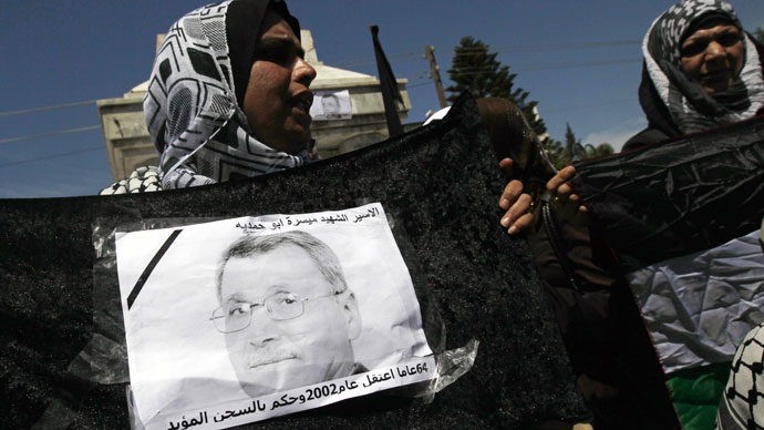 A Palestinian woman holds a picture of Maisara Abu Hamdiyeh, an Israeli-held prisoner who died of cancer while in detention, during a protest against his death in Gaza City on April 2, 2013.(AFP Photo / Mohammed Abed)