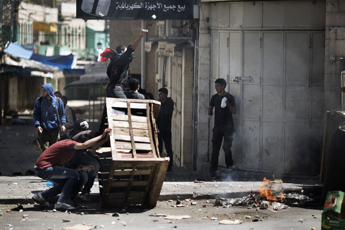 Palestinian demonstrators take cover behind a makeshift barricade during clashes with Israeli troops in the West Bank city of Hebron following the death of a Palestinian prisoner on April 2, 2013.(AFP Photo / Marco Longari)