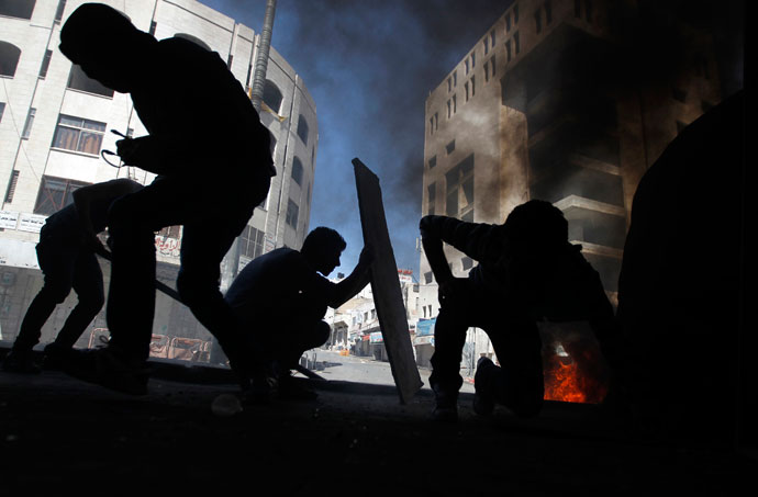 Stone-throwing Palestinian protesters take cover during clashes with Israeli soldiers in the West Bank city of Hebron, after Maysara Abu Hamdeya, a Palestinian inmate died from cancer in an Israeli hospital on Tuesday April 2, 2013.(Reuters / Ammar Awad)