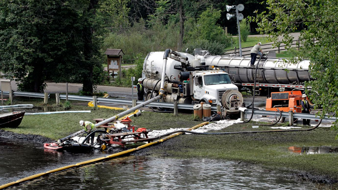 Workers using suction hoses try to clean up an oil spill of approximately 800,000 gallons of crude oil from the Kalamazoo River July 28, 2010 in Battle Creek, Michigan.(AFP Photo / Bill Pugliano)