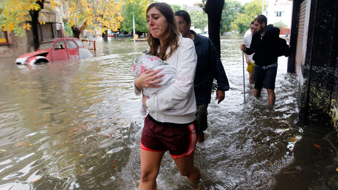 People wade through a flooded street after a rainstorm in Buenos Aires April 2, 2013.(Reuters / Enrique Marcarian)