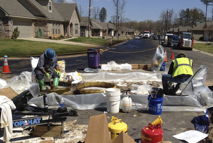 Workers scrub crude oil from their boots in the Northwoods subdivision where an ExxonMobil pipeline ruptured in Mayflower, Arkansas, April 1, 2013. (Reuters)