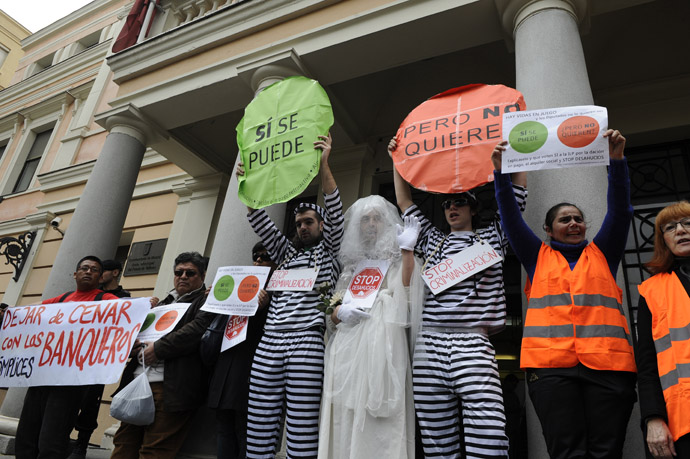 Anti-eviction activists, some of them dressed up as prisoners or as a bride, take part in a protest to demand the vote of a Popular Legislative Initiative (ILP) to stop evictions, regulate dation-in-payment and establish social rents, in front of a municipal building of Vallecas, office of Madrid's deputy Eva Duran, in Madrid on April 3, 2013. (AFP/Photo)