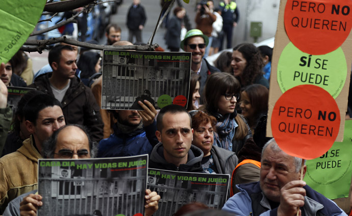 Members of the Mortgage Victims' Platform (PAH) hold placards during a protest in Madrid April 3, 2013. (Reuters)