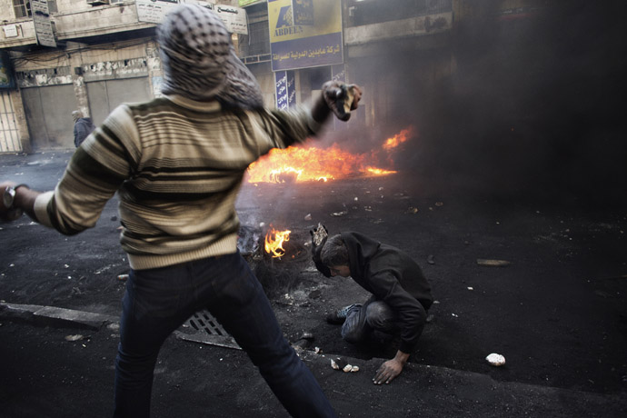 A Palestinian demonstrator throws stones towards Israeli security forces as his comrade breaks stones on the ground during clashes in the West Bank city of Hebron on April 4, 2013. (AFP Photo)