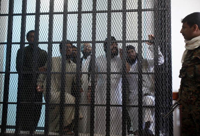 Police troopers (L and R) stand guard as defendants look from behind bars as verdicts are being pronounced at the courtroom of a state security court of appeals in Sanaa February 12, 2013. The court on Tuesday upheld jail sentences of periods between one to five years against seven defendants over al Qaeda links, the state Saba news agency reported. (Reuters)