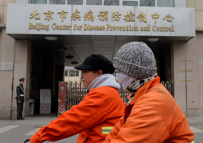 Two women ride past the Beijing Center for Disease Prevention and Control after the arrival there of testing kits for the H7N9 bird flu virus in Beijing on April 4, 2013. (AFP Photo/Mark Ralston)