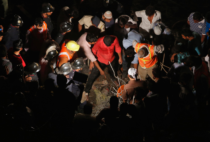 Rescue workers gather around the body of a man who was trapped under rubble at the site of a collapsed residential building in Thane, on the outskirts of Mumbai April 4, 2013 (Reuters / Vivek Prakash)