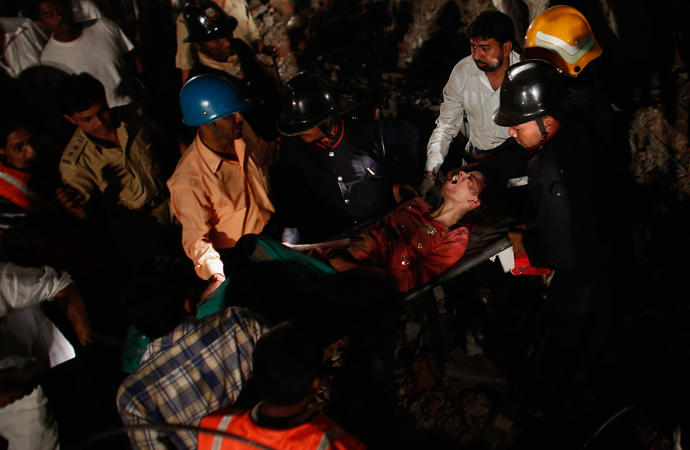 Rescue workers carry a woman who survived from a collapsed residential building in Thane, on the outskirts of Mumbai April 4, 2013 (Reuters / Danish Siddiqui)