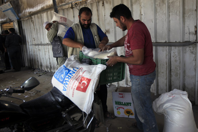 Palestinians collect food supplies from the United Nations Relief and Works Agency (UNRWA) headquarters in Rafah in the southern Gaza Strip (AFP Photo/Said Khatib)