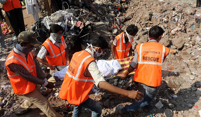 Resue officials and disaster management staff bring out a body from under the rubble and debris at the site of a building collapse at Mumbra in Thane, on the outskirts of Mumbai on April 6, 2013. (AFP Photo / Indranil Mukherjee)