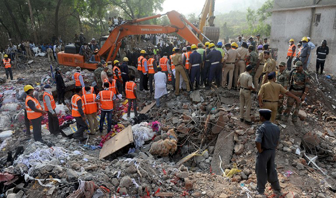 Resue officials and disaster management staff stand on top of the rubble and debris at the site of a building collapse at Mumbra in Thane, on the outskirts of Mumbai on April 6, 2013. (AFP Photo / Indranil Mukherjee)