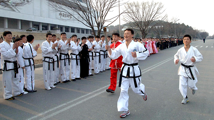 Athletes attend a torch-lighting ceremony for the 5th International Martial Arts Games on Chongchun Street in Pyongyang April 3, 2013. (AFP Photo / KCNA)