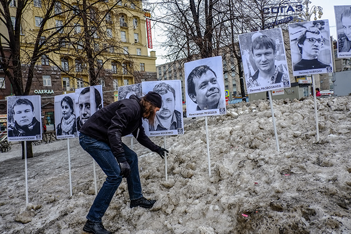 A man stands next to pictures of jailed opposition supporters during a rally in central Moscow on April 6, 2013. (RIA Novosti / Andrei Stenin)