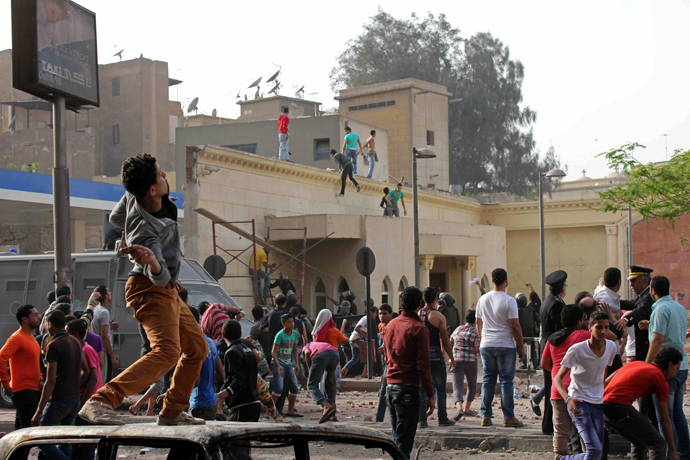 Unidentified Egyptians throw stones towards Coptic Christians during sectarian clashes outside the Egyptian Coptic cathedral in Cairo's Abbassiya neighbourhood on April 7, 2013 (AFP Photo / STR)