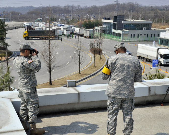 US soldiers take pictures as South Korean trucks return back after they were banned access to Kaesong joint industrial park in North Korea, at a military check point of the inter-Korean transit office in Paju on April 3, 2013. (AFP Photo/Jung Yeon-Je)
