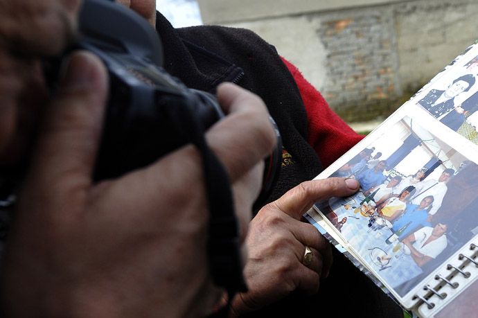 A neighbour shows a family album bearing a picture of the alleged killer in the village of Velika Ivanca, 40 kilometres south of capital Belgrade, on April 9, 2013, where a man shot dead 13 relatives and neighbours, including a two-year-old child, in the country's worst killing spree in two decades.(AFP Photo/Andrej Isacovic)