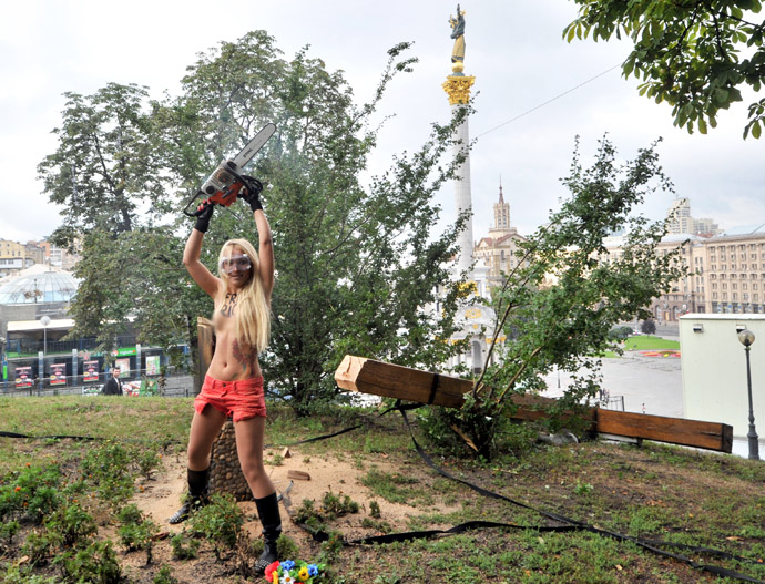 An activist of the Ukrainian feminist group Femen raises a chainsaw after cutting down a cross, erected to the memory of victims of the political repression in Kiev on August 17, 2012. (AFP Photo)