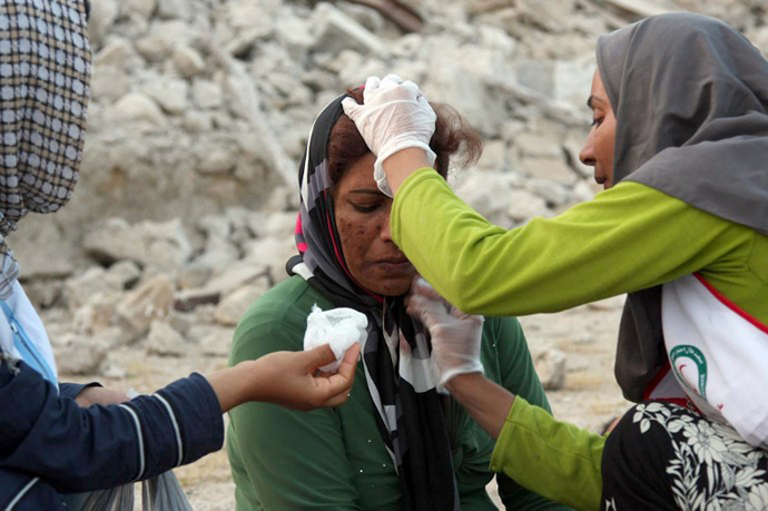 An Iranian woman receives medical treatment from aid workers in the town of Shonbeh, southeast of Bushehr, on April 9, 2013. (AFP Photo / Mohammad Fatemi)