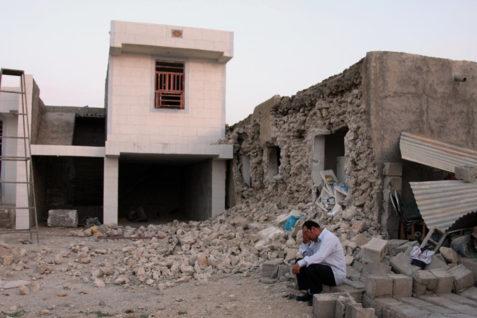An Iranian man squats next to his destroyed house in the town of Shonbeh, southeast of Bushehr, on April 9, 2013 after a powerful earthquake struck near the Gulf port city of Bushehr. (AFP Photo / Mohammad Fatemi)
