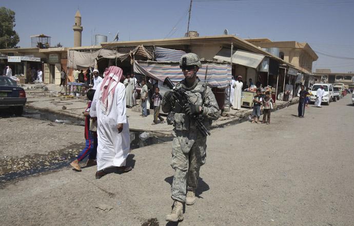 A U.S. soldier on patrol walks past Iraqi residents in Mosul, 390 km (240 miles) north of Baghdad, September 5, 2010. (Reuters/Saad Shalash)