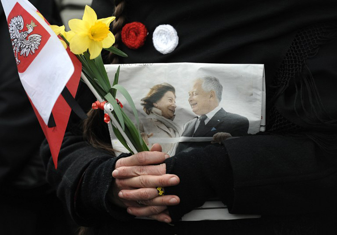 A person holds a Polish flag and a photo of late Polish presidential couple during a public memorial service on Pilsudski square in Warsaw on April 17, 2010. (AFP Photo / Joe Klamar)