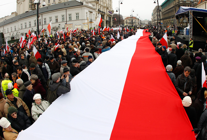 People hold a Polish flag during a remembrance ceremony for the 2010 plane crash that killed former Polish President Lech Kaczynski and 95 others outside of the Presidential Palace in Warsaw April 10, 2013 (Reuters / Peter Andrews)