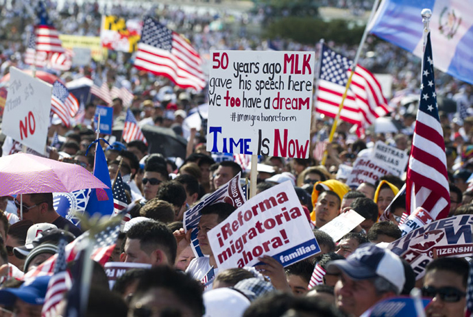 """A man dressed as Uncle Sam poses for photos as tens of thousands of immigration reform supporters march in the """"Rally for Citizenship"""" on the West Lawn of the US Capitol in Washington, DC, on April 10, 2013 (AFP Photo / Saul Loeb)"""