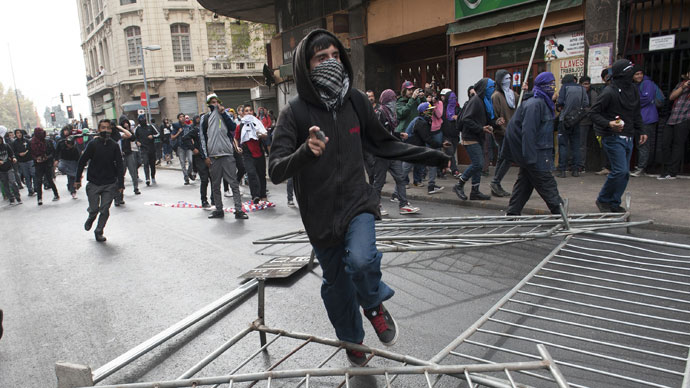 Students clash with riot police during a protest to demand Chilean President Sebastian Pinera's government to improve the public education quality, in Santiago, on April 11,2013.(AFP Photo / Claudio Santana)